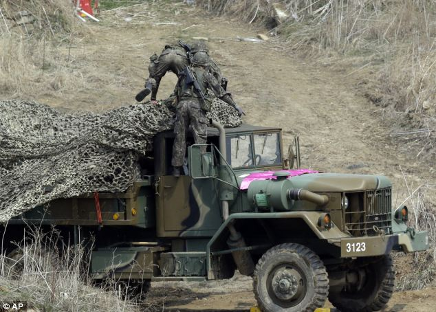 Training: South Korean soldiers place a camouflage net over their military vehicle during a military exercise near the border village of Panmunjom in Paju