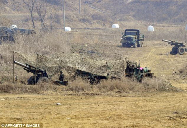 Duties: South Korean soldiers man cannons at a military training field after North Korea dramatically escalated its warlike rhetoric today