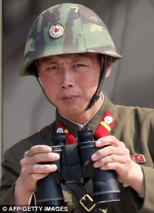 A North Korean soldier looks through binoculars at the truce village of Panmunjom in the demilitarized zone (DMZ) dividing the two Koreas