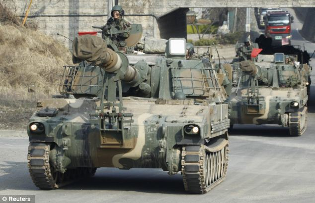 Drills: South Korean soldiers ride the tanks through the streets on their way to take part in military drills