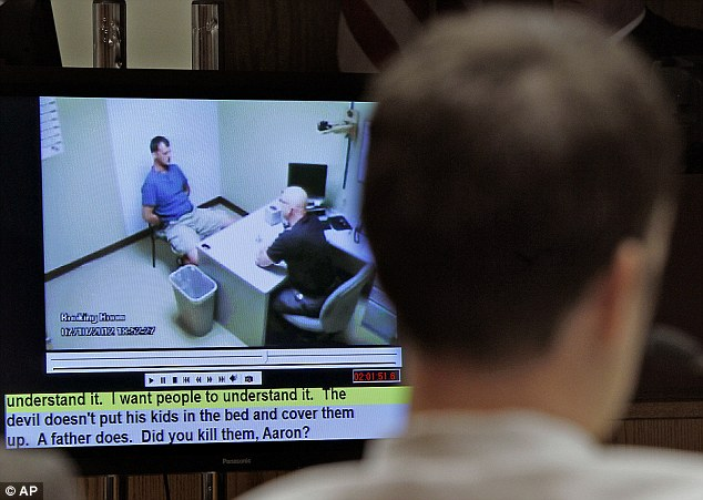 Searching for a reason: Aaron Schaffhausen, back to camera, watches as jurors are shown a video on Wednesday of River Falls Police Detective Charles Golden initial interrogation after his three daughters were found dead in their beds