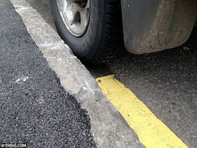 Comical: The yellow lines stop at the wheel of the car and then continued at the other side