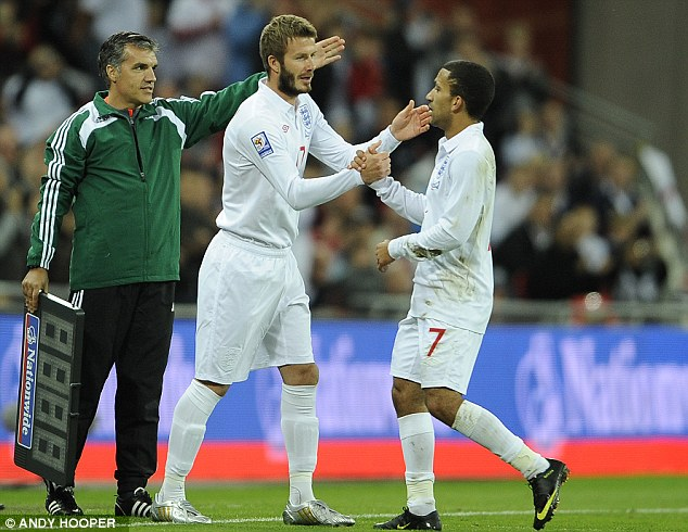 Yesterday's man: David Beckham replaces Aaron Lennon on his last England appearance in 2009 - indeed, he has been on the England bench more recently in a non-playing capacity, at the 2010 World Cup (below)