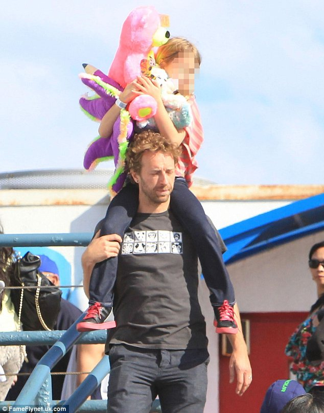 Fun daddy: Chris Martin treats his two children to a fun day out at Santa Monica pier, where they enjoyed the fun fair on offer on Thursday