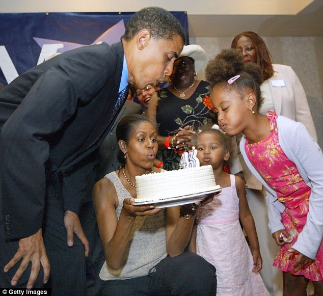 Holding it all together: Mr Obama blows out the candles on his 43rd birthday cake while he was out on the campaign trail for the Senate race in 2004