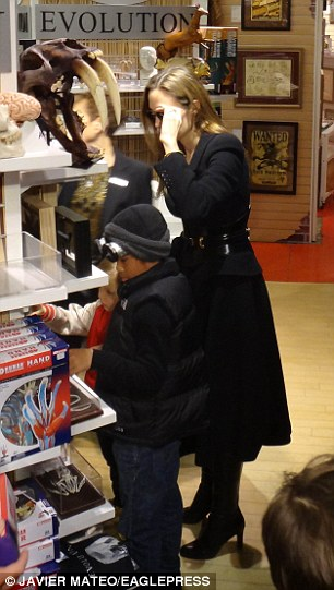 Real science: Angelina's hair looked almost blonde as she knelt down with her sons in the science section