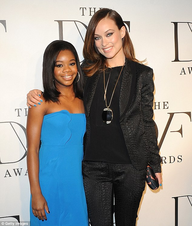 Gal pals: Olivia, seen with Olympic champ Gabrielle Douglas, accessorised her feminist look with a DVF 'Flirty Lips Mini' clutch, a blue manicure, and a massive black medallion