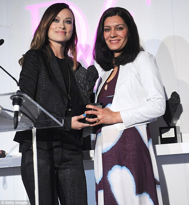 Grin when you're winning: Olivia shared a smile with Andeisha Farid as she handed over her gong