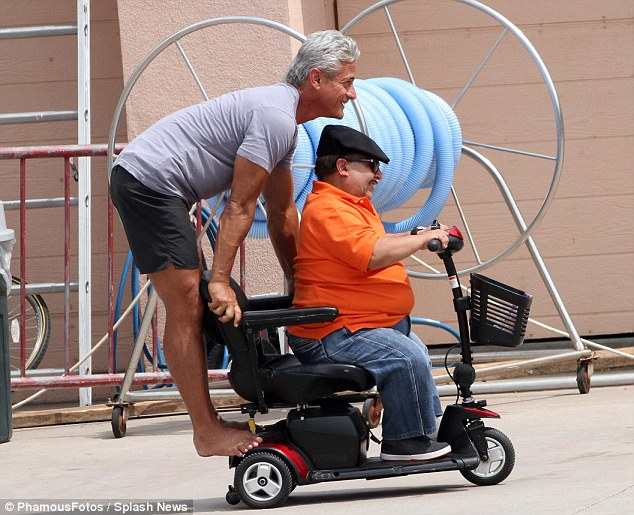 Come ride with me: Chuy gives his former trainer a lift on the back of his motorised scooter