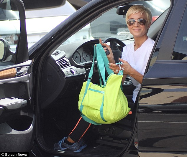What's in the bag?: The country singer smiles as she holds up her neon gym bag