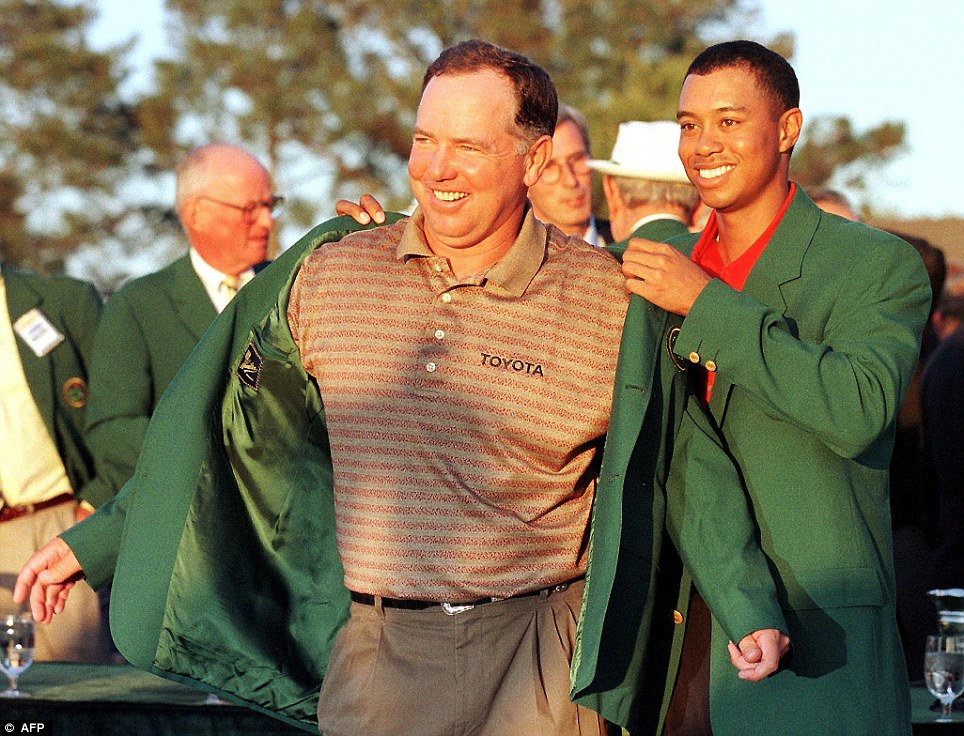 Mark O'Meara (left) gets the green jacket from the previous year's champion, and his great friend, Tiger Woods
