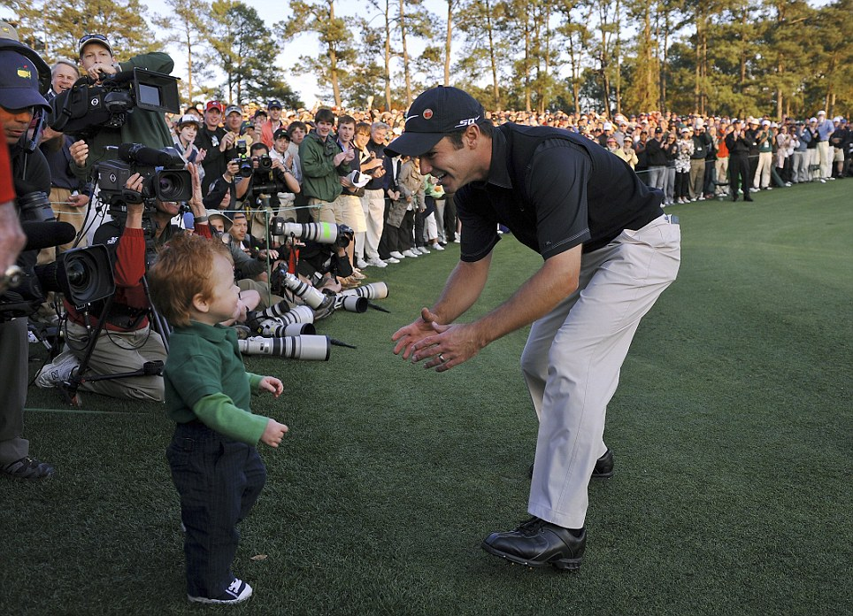 Trevor Immelman reaches for his son, Jacob Trevor, after winning the Masters