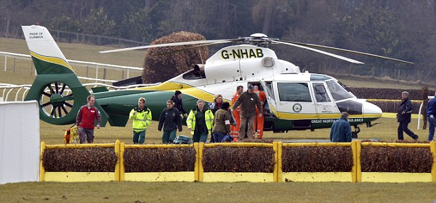 The Great North Air Ambulance prepares to take off from Hexham Racecourse next to the fence where Grand National winning jockey Ryan Mania fell today, just 24 hours after he stormed to victory at Aintree on 66-1 outsider Auroras Encore.