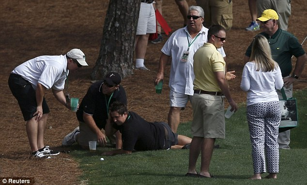 Down and out: The fan was seen clutching his head after he was knocked to the ground
