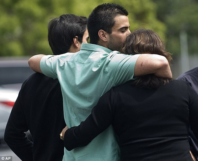 Relief: Nicolas Cendoya, center, hugs his brother, left, and mother, right, after he was released from Mission Hospital today
