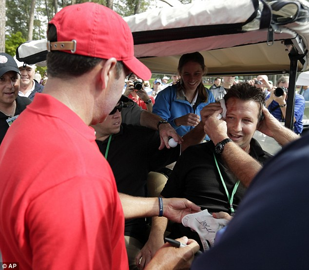Sign here: The Spaniard hands over his golf club with his signature to the injured fan