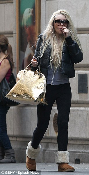 Disheveled: Amanda was bundled up in a grey hoodie under a black puffy coat, black leggings, and fur-lined Uggs as she hauled an over-stuffed gold Louis Vuitton bag