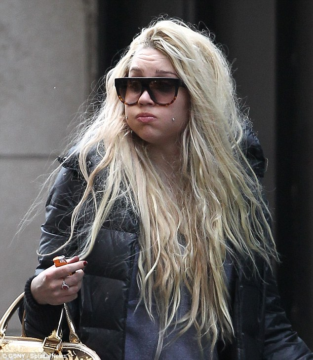 Holding it in: The troubled starlet looked disheveled, mostly due to the cascade of platinum blonde extensions all matted and tangled around her shrinking frame