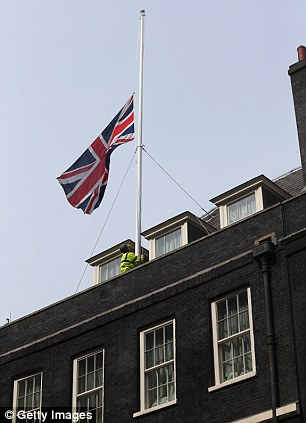 A workman lowers the Union Flag flying above Downing Street to half-mast at the news of the death of former British prime Minster Baroness Thatcher