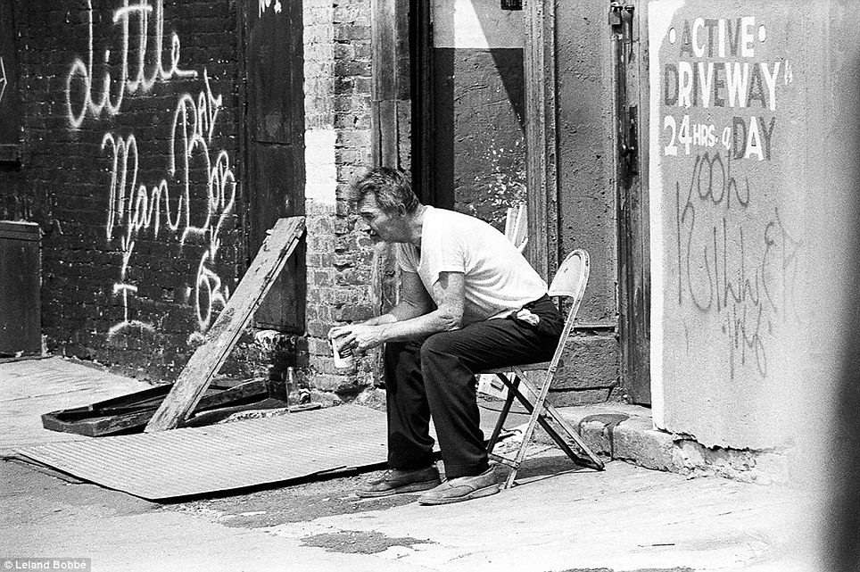 Down time: This man waits for nothing in particular as he drinks a beer in the Bowery in Manhattan