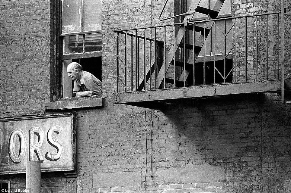 In Hell's Kitchen, a man peers out of his apartment building from an old, battered window