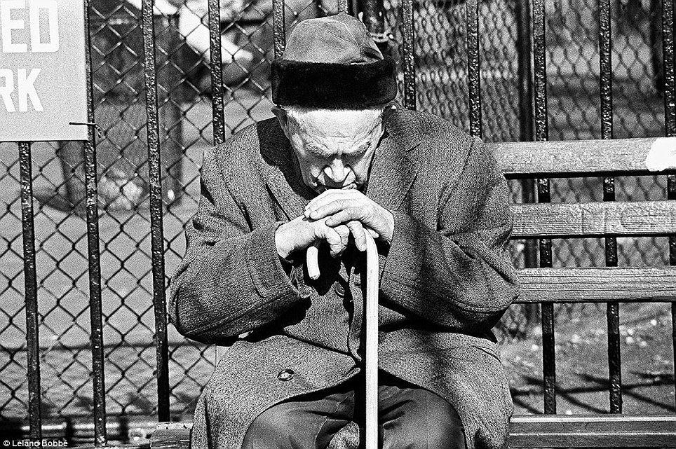 In the Lower East Side, an old Jewish man leans on his cane at a park bench