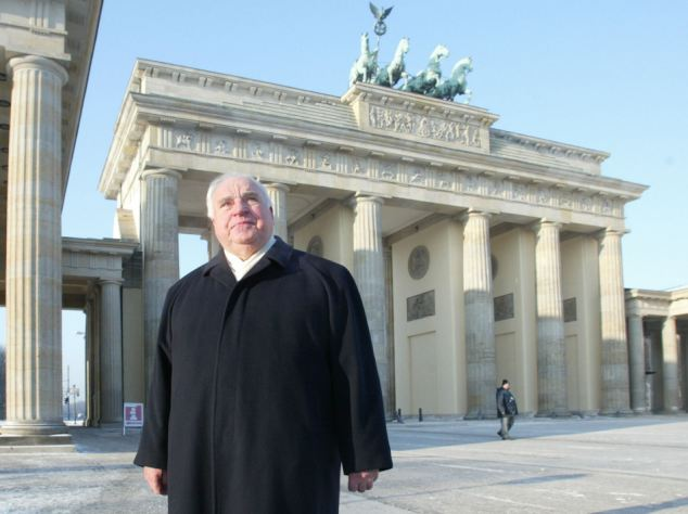 'I had to be forceful': Former German chancellor Helmut Kohl, pictured above in front of the Brandenburg Gate during a private walk in Berlin, has revealed he 'acted like a dictator' to bring in the euro