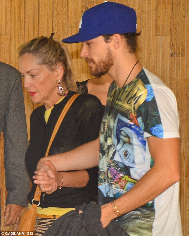 Need a hand love? Sharon Stone receives a helping hand from her toyboy beau Martin Mica on Sunday as they leave their hotel in Brazil to have dinner