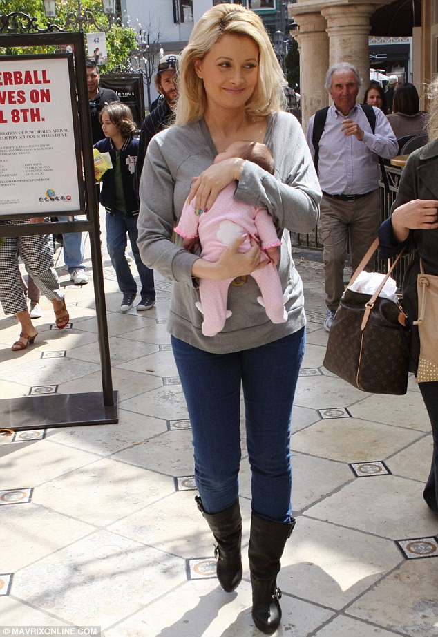 Careful mother: Holly Madison cradled her daughter Rainbow as they went on a shopping trip to The Grove in West Hollywood on Monday