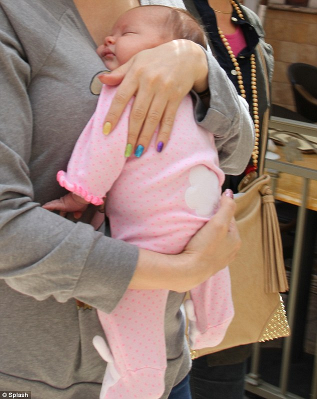 Sweet dreams: The star, who had a rainbow manicure to match her daughter's name, kept her little one close