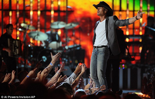 Soaking up the applause: Sporting a cowboy hat, jeans and a blazer, Tim looked full of energy as he pumped up the crowd