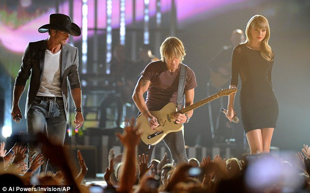Intrepid trio: Taylor joined Tim McGraw and Keith Urban on stage in a repeat performance of the ACMs