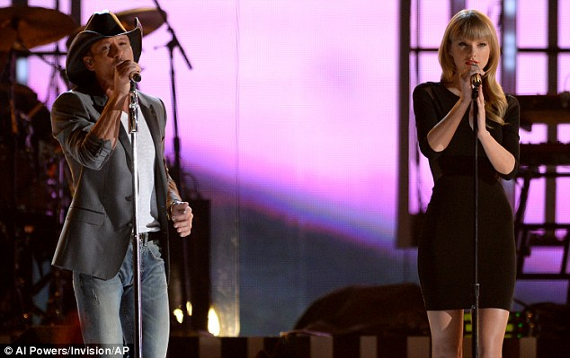 Country crossover: Taylor looked more pop star than country singer bin comparison to Tim's appearance on stage