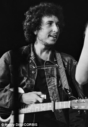 Bob Dylan is standing on stage with his guitar during the 1971 Concert for Bangladesh