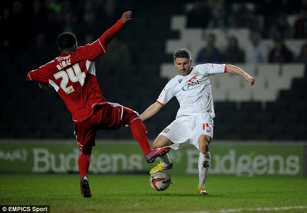 Comfortable: Ryan Lowe (right) slots home MK Dons' second goal against Swindon