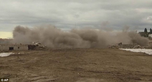 End of an era: The resilient 1,000-ton smokestack finally fell hours after the planned demolition, kicking up a huge cloud of dust