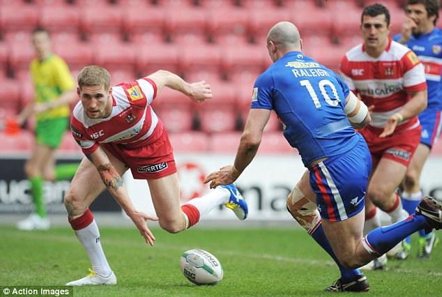 Hat-trick hero: Sam Tomkins (left) scores one of his three tries against Wakefield