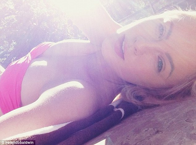Bathing beauty: The 17-year-old gave herself a soft glow as she soaked up the sun