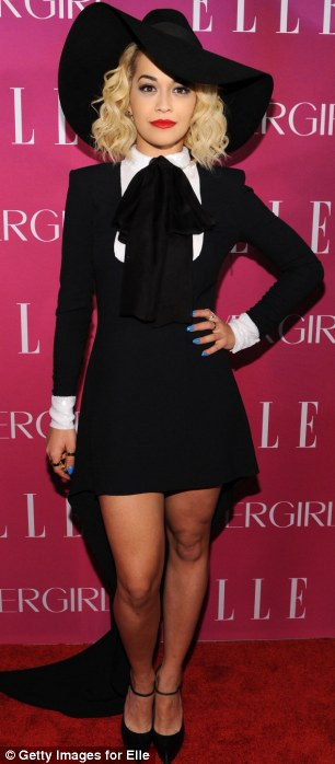 The young pretender: Rita Ora cut a striking figure in floppy black hat and smart black and white suit, complete with train, dwarfing Kelly Rowland's ensemble at the fourth Annual ELLE Women in Music Celebration in New York on Wednesday