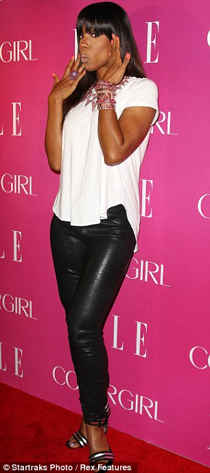 Leather legs: Kelly sported clinging black trousers, a white T-shirt and black and silver strappy heels for the event