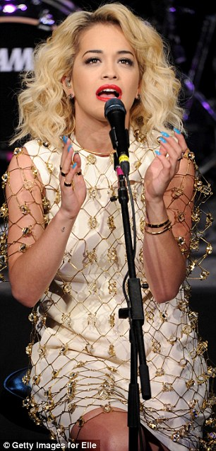 Going for gold: Rita changed into a champagne coloured dress with metallic net-like overlay as she performed
