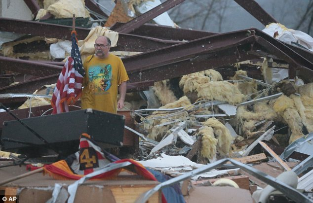 Destruction: Benjamin Pierce, a patron of the Botkinburg Foursquare church, sifts through the wreckage of the church