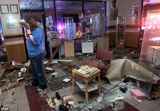 Damage: Kristin Little, manager of the Ferguson Optical shop in Hazelwood, talks with a friend on the phone as she describes the damage
