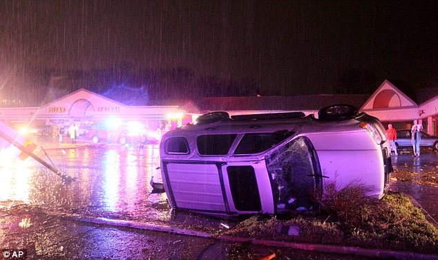 Chaotic scene: An overturned car is pictured in Hazelwood, Missouri, after the storm blew through the area