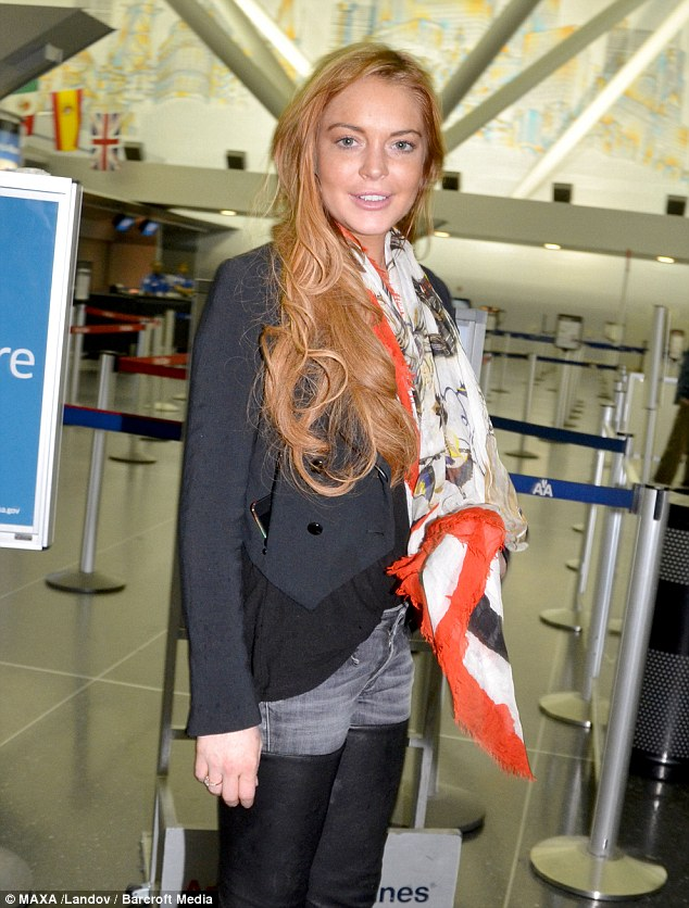 Mix and match: Lindsay Lohan arrived at JFK International Airport to catch a flight wearing denim leather chap trousers on Wednesday