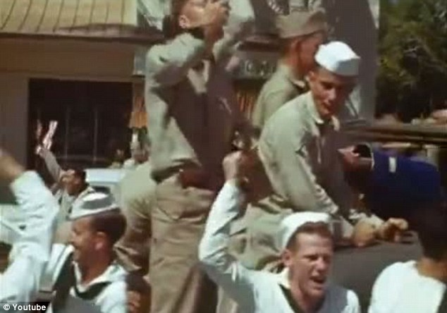 Celebrations: US Navy personnel pack onto a car an punch the air with delight as they celebrate the end of World War Two