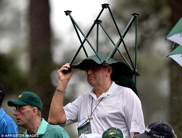 Forgotten your brolly? A patron takes cover in the rain during the second round