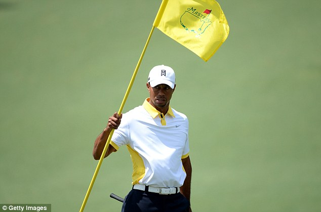 Flag bearer: Tiger Woods on the second hole as he made a steady start to his second round