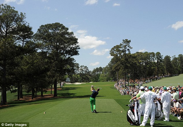 Familiar pose: Donald hits his shot on the third tee on Friday