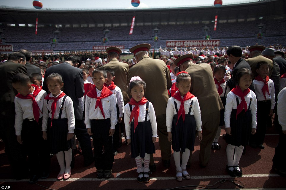 First steps into tyranny: North Korean children stand in line while officers tie bandanas around their necks at a ceremony to induct them into the Korean Children's Union